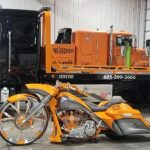 Olson Towing Truck next to a motorcycle chopper
